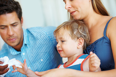 Buy stock photo Closeup of family sitting together with father giving tissue paper to his son
