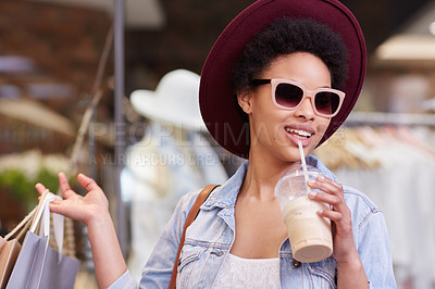 Buy stock photo Cropped shot of a young woman drinking a smoothie while shopping