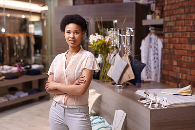 Buy stock photo Cropped portrait of a young woman standing with her arms folded in her clothing boutique