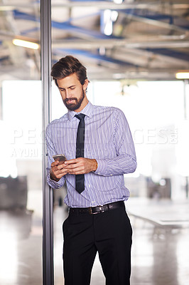 Buy stock photo Shot of a young executive using his cellphone while standing in the office