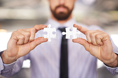 Buy stock photo Cropped shot of a businessman holding a puzzle piece in each hand