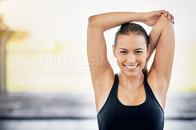 Buy stock photo Cropped portrait of a young woman stretching before a workout