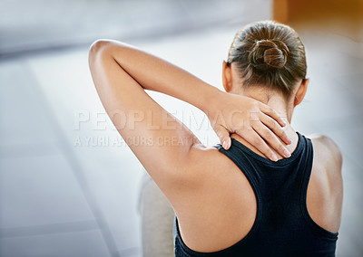 Buy stock photo Rearview shot of a young woman rubbing her neck during a workour