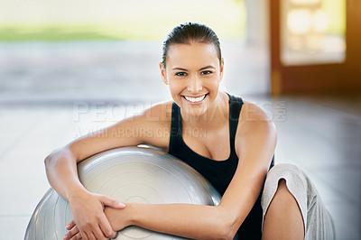 Buy stock photo Cropped portrait of a young woman sitting against her exercise ball