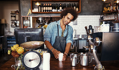 Buy stock photo Shot of a young barista preparing a cup of coffee at a cafe