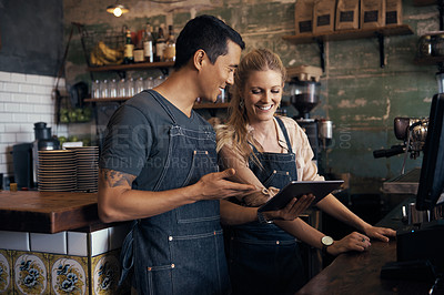 Buy stock photo Shot of two baristas using a digital tablet together at a cafe