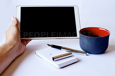 Buy stock photo High angle shot of a tablet in a woman's hand and a cup of coffee on her table