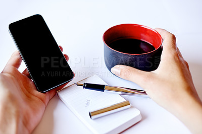 Buy stock photo High angle shot of a cellphone in a woman's hand and a cup of coffee on her table