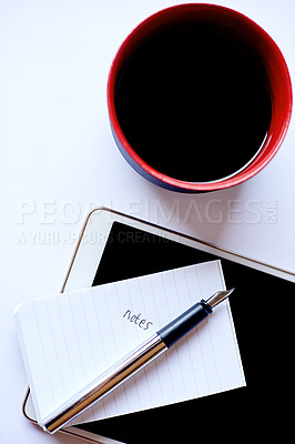 Buy stock photo High angle shot of a coffee, a tablet and a notepad on a desk