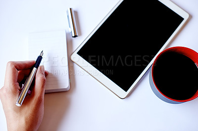 Buy stock photo High angle shot of a businesswoman writing on a notepad