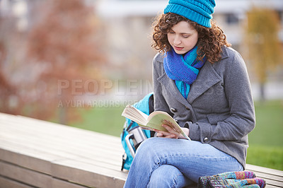 Buy stock photo Shot of a young woman reading a book while sitting outside on a bench