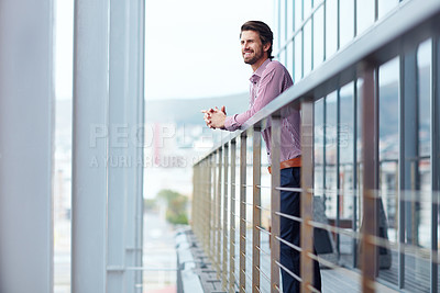 Buy stock photo Shot of a happy young businessman standing on the balcony of an office building