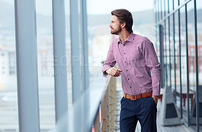 Buy stock photo Shot of a thoughtful young businessman standing on the balcony of an office building