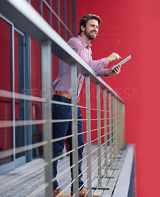 Buy stock photo Shot of a young businessman using a digital tablet on the balcony of an office building