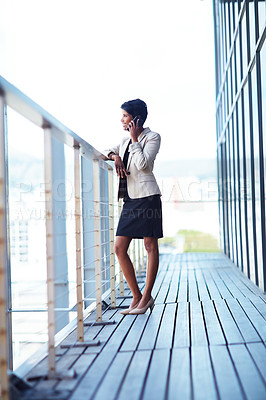 Buy stock photo Shot of a young businesswoman talking on a phone outside of an office building