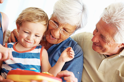 Buy stock photo Cute little kid playing a toy with his family