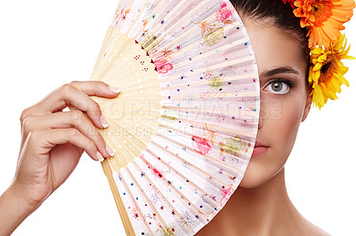 Buy stock photo Cropped portrait of a beautiful young woman wearing a crown of flowers while holding a fan in front of her face