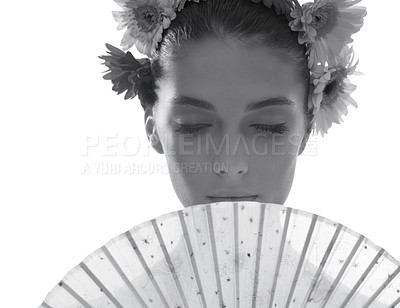 Buy stock photo Black and white shot of a beautiful young woman wearing a crown of flowers while holding a fan in front of her face