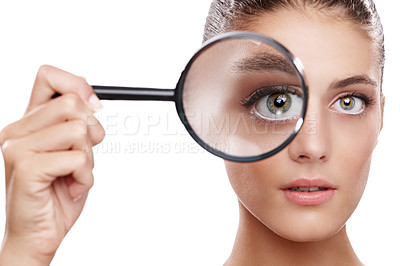 Buy stock photo Studio shot of a beautiful woman with a magnifying glass in front of her eye