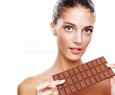 Buy stock photo Studio portrait of an attractive young woman holding a slab of chocolate