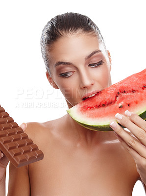 Buy stock photo Studio shot of a young woman eating a slice of watermelon while eying out a slab of chocolate