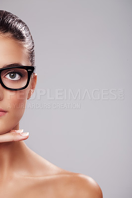 Buy stock photo Cropped studio portrait of a beautiful young woman wearing glasses against a gray background