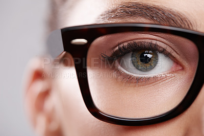 Buy stock photo Closeup studio portrait of a young woman wearing glasses against a gray background