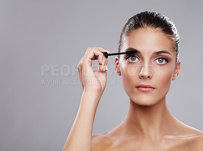 Buy stock photo Studio shot of a beautiful young woman applying makeup  against a gray background