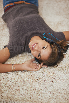 Buy stock photo Portrait of a young woman relaxing at home and listening to music