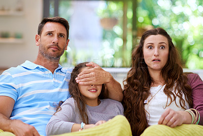 Buy stock photo Cropped shot of a father covering his daughter's eyes while watching a movie