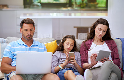 Buy stock photo Cropped shot of a family sitting on the sofa and using their smart devices