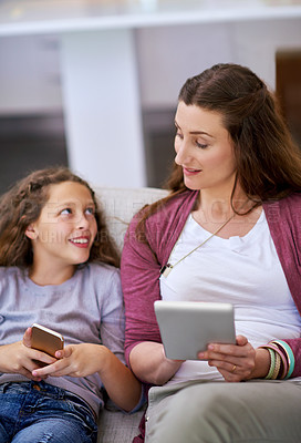 Buy stock photo Cropped shot of a young girll and her mother sitting on the sofa and using their smart devices