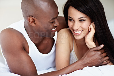 Buy stock photo Shot of an affectionate young couple lying in bed together