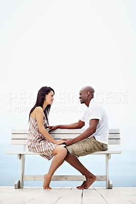 Buy stock photo Shot of a young couple talking together while sitting on a bench by the ocean