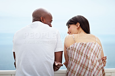 Buy stock photo Rearview shot of a young couple leaning on a railing by the ocean