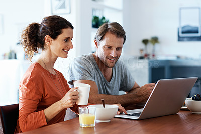 Buy stock photo Shot of a smiling couple using a laptop while eating breakfast