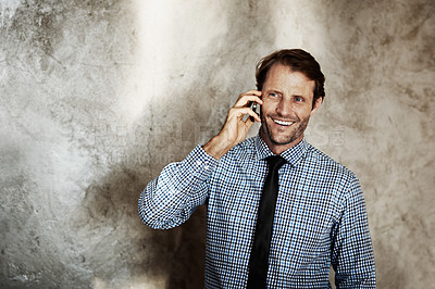 Buy stock photo Shot of a man talking on his cellphone while standing against a wall