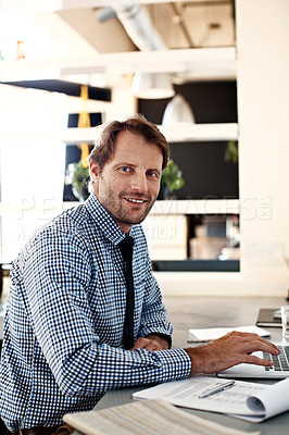 Buy stock photo Portrait of a smiling man working on a laptop