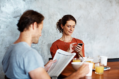 Buy stock photo Shot of a couple eating breakfast at their kitchen table while reading the paper and using a cellphone