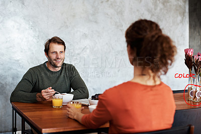 Buy stock photo Shot of a smiling couple eating breakfast at their kitchen table