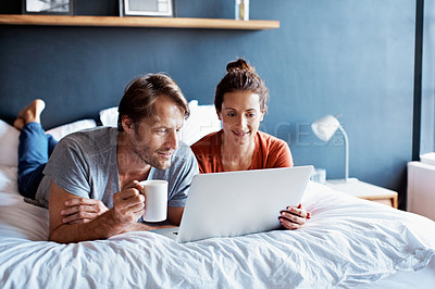 Buy stock photo Shot of a smiling couple lying in bed together using a laptop