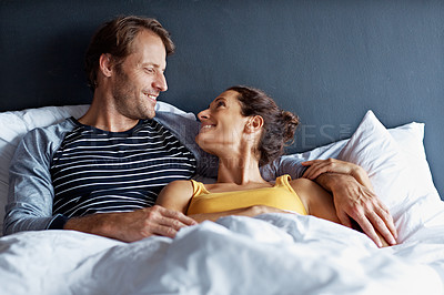 Buy stock photo Shot of a content couple lying in bed together