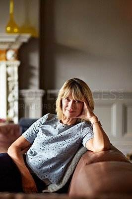 Buy stock photo Portrait of a mature woman relaxing on her living room sofa