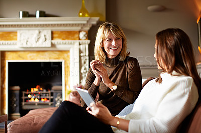 Buy stock photo Shot of a woman talking with her daughter on the living room sofa