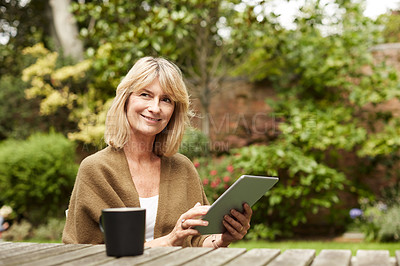 Buy stock photo Portrait of a mature woman sitting in her yard drinking tea and using a digital tablet