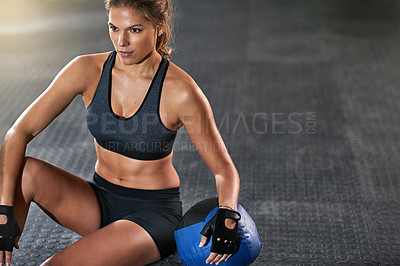Buy stock photo Cropped shot of a young woman sitting beside a kettle bell after her workout