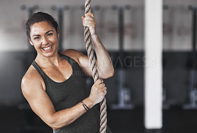Buy stock photo Cropped portrait of a young woman climbing a rope at the gym