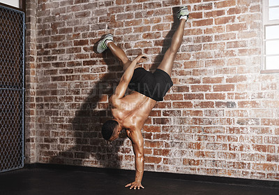 Buy stock photo Rearview shot of a young man working out in the gym