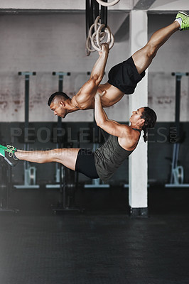 Buy stock photo Full length shot of two young athletes working out on the gymnastics rings