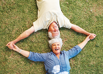 Buy stock photo Top view of senior couple holding hands and lying on the grass with heads together